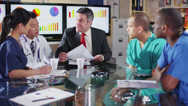 Diverse group of medical professionals in a meeting with a hospital executive Stock Footage