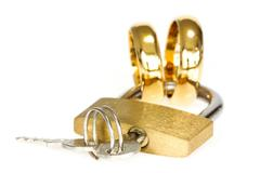 padlock with golden rings on white background - stock photo