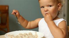 little girl eats porridge - stock footage