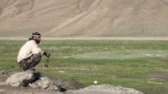 Tajik muslim man contemplating, looking out over grasslands Stock Footage