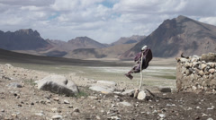 Scarecrow in beautiful remote landscap, Tajikistan settlement, Central Asia Stock Footage
