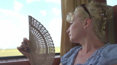 Young woman with hand fan in hot day, train, summer, blonde girl Stock Footage