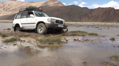 Landcruiser stuck in swamp in remote Pamir mountains in Tajikistan Stock Footage