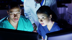 Medical team working late at a computer and discussing what they see on screen - stock footage