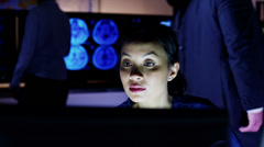 Female medical professional working late in front of a computer screen - stock footage