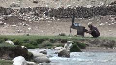 Woman prepares tea on old stove outside, in small village in Tajikistan Stock Footage