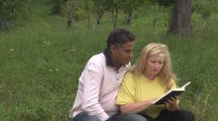 Young happy romantic couple enjoy read kiss book park garden rural woman man Stock Footage