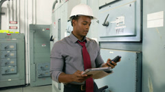 Engineer with tablet and cell in electrical room Stock Footage