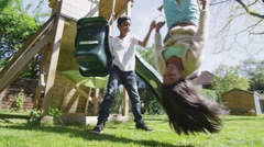Cute young brother and sister playing on the swings on a hazy summer day Stock Footage