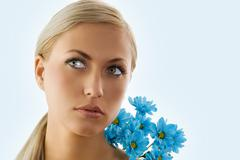 Stock Photo of blond girl and blue daisy