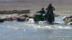 Old motorbike drives through river in Pamirs Stock Footage