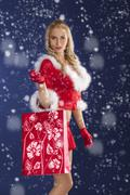pretty girl santa claus standing with shopping bag - stock photo
