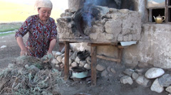 Woman uses traditional oven in small settlement in the Pamir mountains Stock Footage