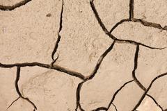 Säröillä kuivaan maahan kuivuus konsepti tausta Kuvituskuvat