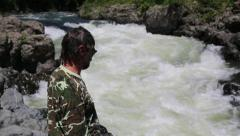 Hiker looking at the raging torrent of the mountain river Stock Footage
