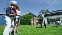 Family & friends of many generations playing sports in the garden on a sunny day Stock Footage