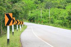 road signs warn drivers for ahead dangerous curve - stock photo