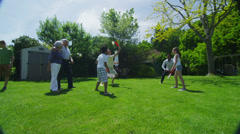 Family & friends of many generations playing sports in the garden on a sunny day - stock footage