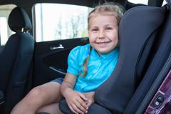 happy smiling young girl sitting in infant restraint seat in car - stock photo
