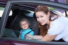 Child sitting in baby car seat and mother helping Stock Photos