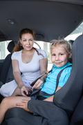 mother helping daughter to fasten car safety belt in restraint seat - stock photo