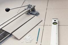 small tile-cutter with laying tiles, pencil and level tube on floor - stock photo