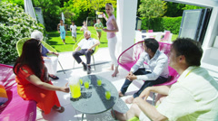 Diverse group of family & friends enjoy refreshment in the garden on a sunny day Stock Footage