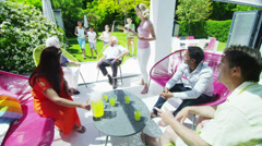 Diverse group of family & friends enjoy refreshment in the garden on a sunny day - stock footage
