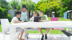 Young friends in the garden on a summer day playing with a computer tablet - stock footage