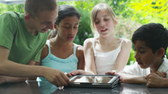 Young friends in the garden on a summer day playing with a computer tablet Stock Footage