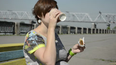 Pregnant woman on the waterfront eating sandwich Stock Footage