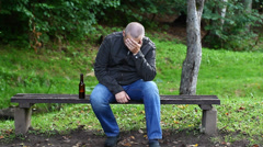 Man with a bottle in the park on a bench episode 1 Stock Footage
