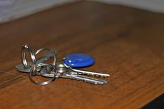 Keys with a rings lay on the brown wood table Stock Photos