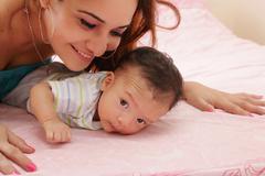 hispanic mother and her newborn baby - stock photo