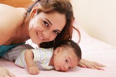 Hispanic mom lying down on bed and holding her infant son Stock Photos