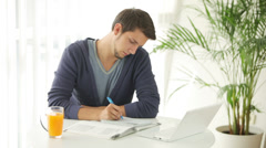 University student sitting at table and studying with laptop Stock Footage