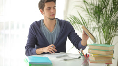 University student sitting at table and writing in notebook Stock Footage