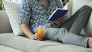 Stock Video Footage of Young man sitting on couch reading book and drinking juice