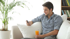 Cheerful guy sitting on sofa using mobile phone and drinking juice Stock Footage