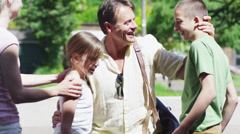 Loving father returns home from a trip to be greeted by his family - stock footage