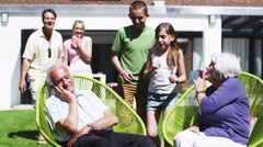 Grandfather plays a trick on his family as they sit in the garden at home Stock Footage