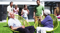 Grandfather plays a trick on his family as they sit in the garden at home - stock footage