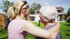 Daughter and her elderly mother bond as they watch the family play in the garden - stock footage