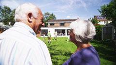 Loving senior couple embrace as they watch their family play in the garden - stock footage