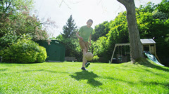 Active young boy practising his soccer skills outdoors on a sunny day - stock footage