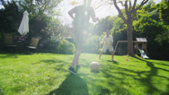 Stock Video Footage of Young boy playing soccer with his father outdoors on a sunny day