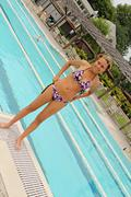 Atractive Young Woman Standing by Pool - stock photo
