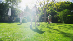 Young girl playing soccer with her family outdoors on a sunny day Stock Footage
