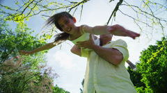 Young girl being held and spun around by her father outdoors on a sunny day Stock Footage