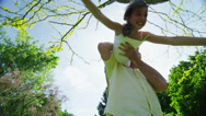 Stock Video Footage of Young girl being held and spun around by her father outdoors on a sunny day